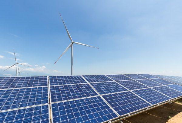 solar panel and wind turbine against a clear sky