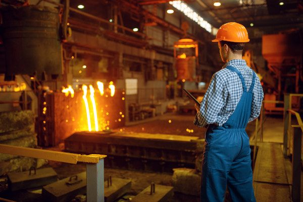 Master steelmaker in helmet at furnace with liquid metal, steel factory, metallurgical or metalworking industry, industrial manufacturing of iron production on mill